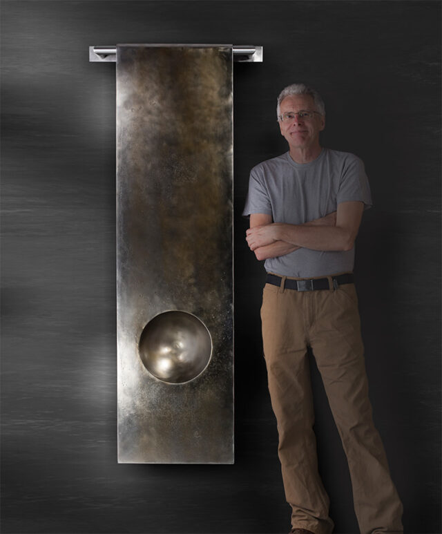Artist, Doug Lochner standing next to his artwork Gravity 2.0 & Trinity